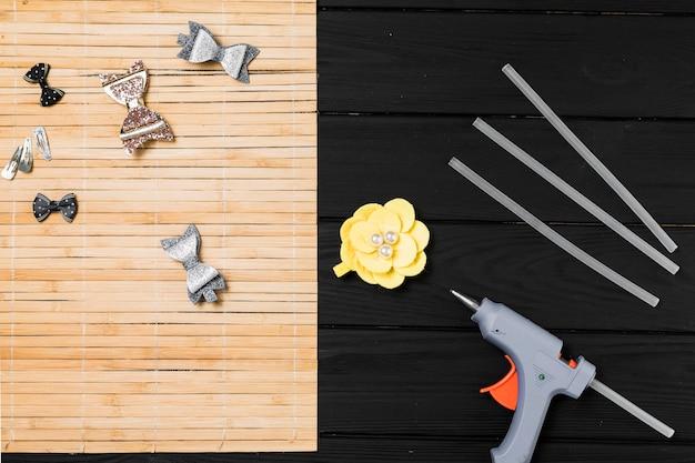 Lindo grampo de cabelo e pistola de cola quente na mesa de madeira preta Foto gratuita