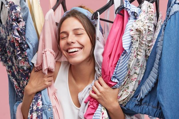 Lindo jovem europeu feminino shoppaholic fechando os olhos de prazer e diversão, mantendo diferentes roupas luxuosas e elegantes em seu guarda-roupa depois de boas compras no shopping da cidade com os amigos Foto gratuita
