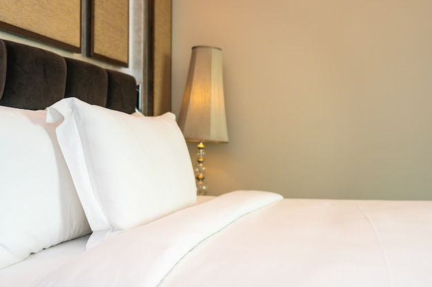 Lindo luxuoso travesseiro branco confortável e decoração de cobertor no interior do quarto Foto gratuita