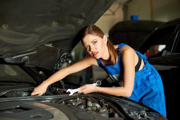 Lindo mecânico feminino repara o carro com uma chave inglesa. Foto Premium