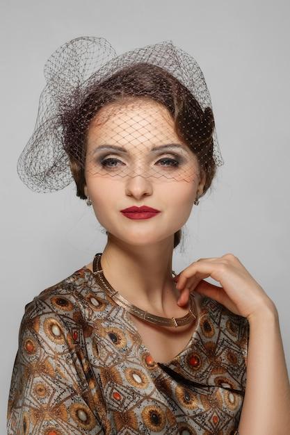 Lindo modelo com lábios vermelhos de esteira e véu sobre os olhos em vestido de seda. limpe o rosto fresco da menina bonita com maquiagem natural. Foto Premium
