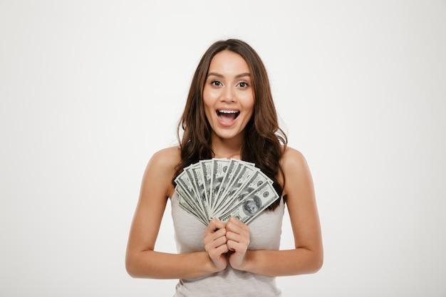 Lindo modelo feminino morena com cabelos longos, segurando o leque de notas de 100 dólares, sendo rico e feliz sobre parede branca Foto gratuita