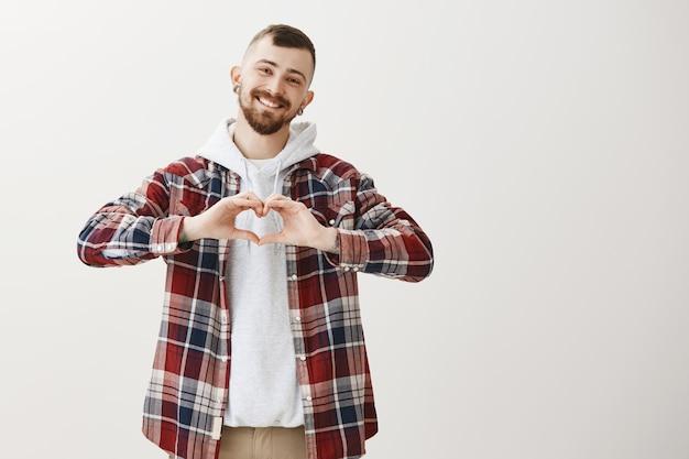 Lindo namorado adorável mostrando gesto de coração e sorrindo fofo Foto gratuita