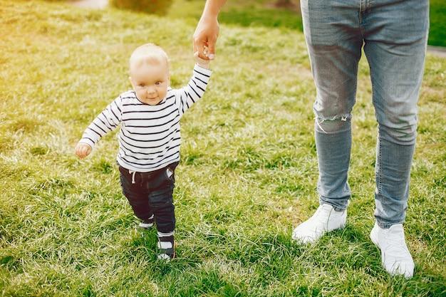 Lindo pai alto e elegante em uma camisola e jeans está batendo com seu pequeno filho doce Foto gratuita
