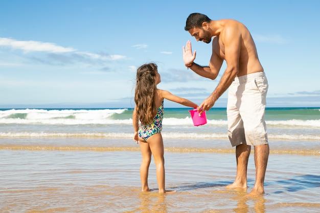 Lindo pai e filha pegando conchas com balde na praia juntos, dando mais cinco Foto gratuita