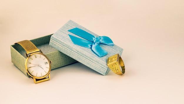 Lindo relógio de ouro e anel na caixa de presente com fita azul Foto Premium