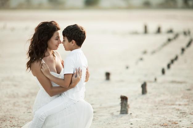 Lindo retrato de mãe e filho na areia, vestido com roupas brancas, olhando um ao outro nos olhos Foto gratuita