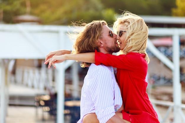 Lindo retrato ensolarado de verão ao ar livre de um jovem casal elegante enquanto se beijava e se abraçava na rua Foto gratuita