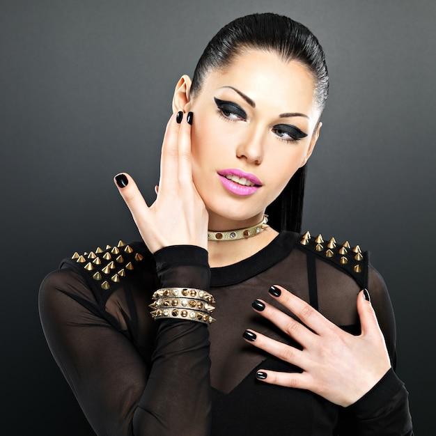 Lindo rosto de mulher fashion com unhas pretas e maquiagem brilhante. garota sexy e elegante com pulseira de espinhos no pescoço Foto gratuita