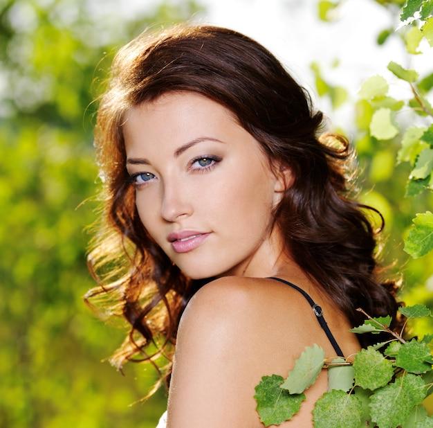 Lindo rosto de uma jovem mulher sexy posando perto de uma árvore verde na natureza Foto gratuita