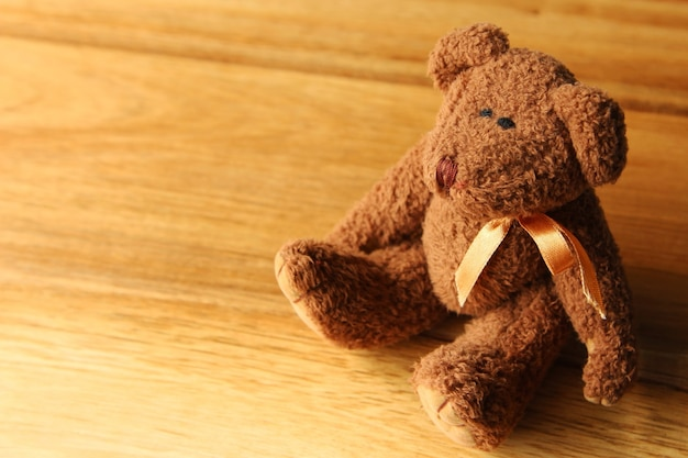 Lindo ursinho de pelúcia em uma superfície de madeira Foto gratuita
