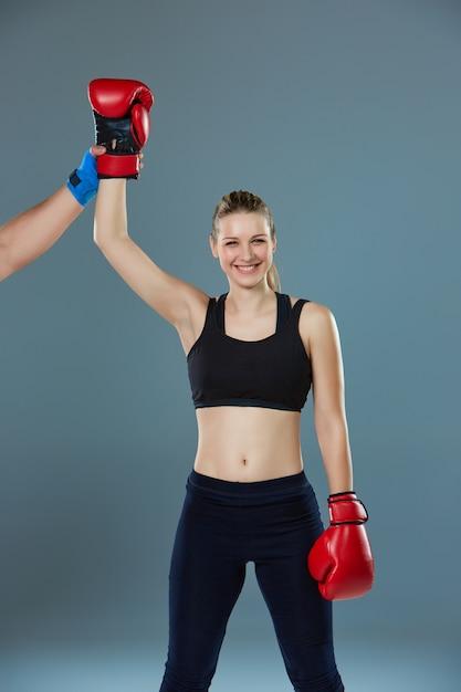 Lindo vencedor. mulher de cabelos loiros em luvas de boxe vermelhas em pé no fundo cinza Foto gratuita