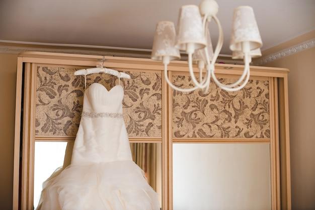 Lindo vestido de noiva pendurado em um guarda-roupa Foto Premium