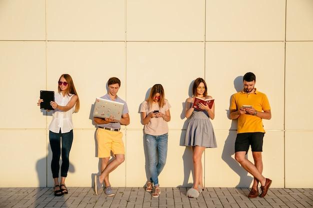 Lindos jovens estudantes estão usando gadgets, lendo livro e sorrindo Foto gratuita