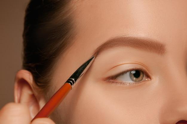 Lindos olhos femininos com maquiagem e pincel Foto gratuita