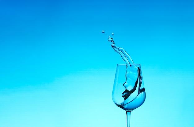 Lindos salpicos de água em uma taça de vinho, com filtro azul, fechem com espaço de cópia. Foto Premium