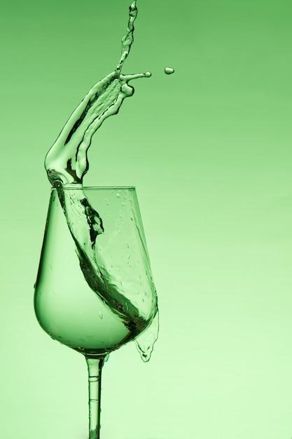 Lindos salpicos de água em uma taça de vinho, com filtro verde, fechem com espaço de cópia. Foto Premium