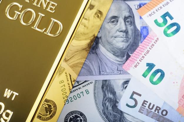 Lingote do lingote do metal do ouro no fundo do dólar e das euro- contas. Foto Premium