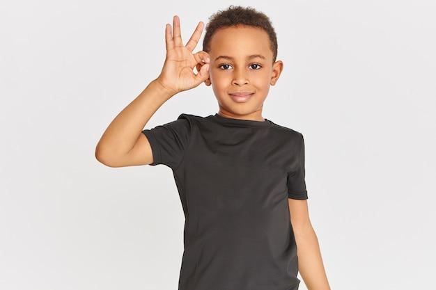 Linguagem corporal. retrato de um garotinho de pele escura, simpático e positivo, usando uma camiseta conectando o indicador e o polegar, fazendo um gesto de aprovação, mostrando um sinal de ok, dizendo que está tudo bem Foto gratuita