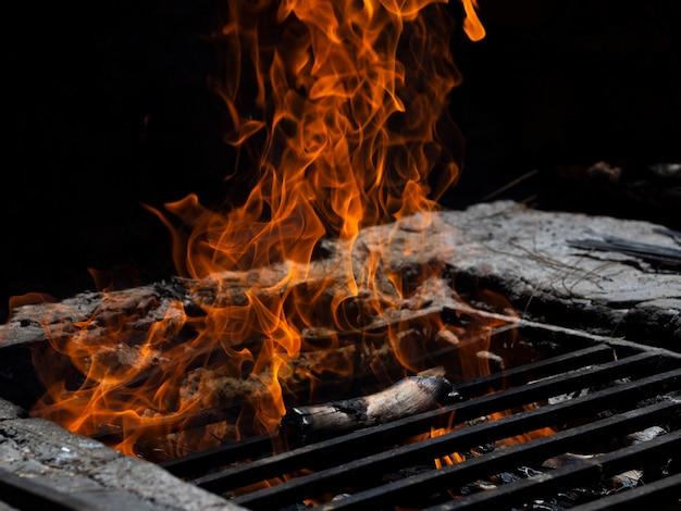 Línguas de fogo na treliça na fogueira na escuridão Foto Premium