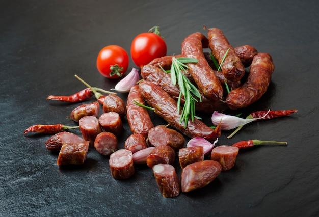 Linguiça defumada com alecrim, pimenta, tomate e alho no preto Foto Premium