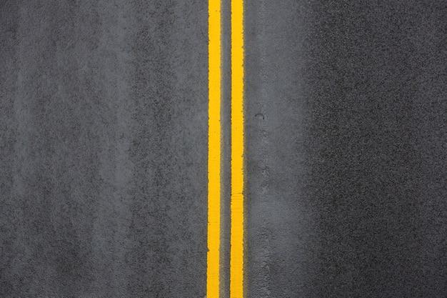 Linha contínua dupla amarela. marcações rodoviárias no asfalto na rua de manhattan, na cidade de nova york Foto Premium