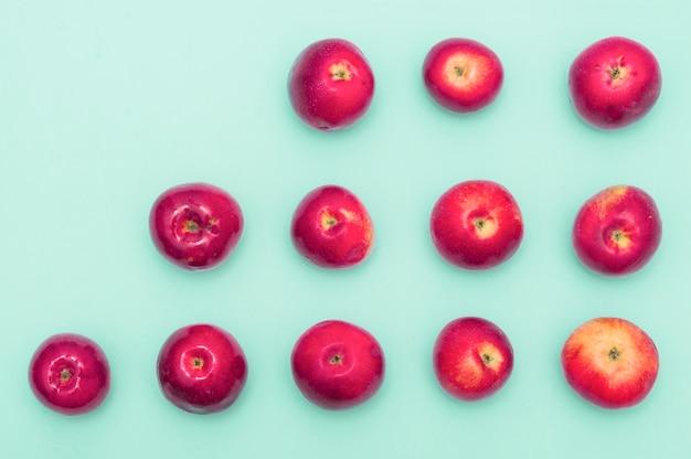 Linha de aumento de maçãs vermelhas contra o fundo azul Foto gratuita