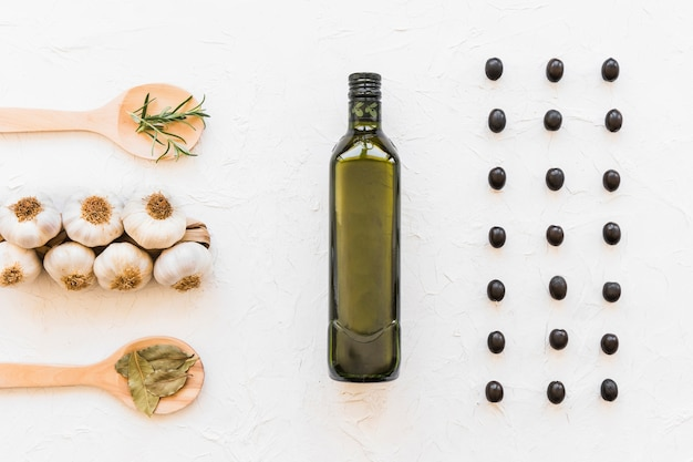 Linha de azeitonas pretas com frasco de óleo, bulbos de alho e ervas no pano de fundo texturizado branco Foto gratuita