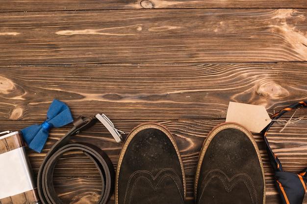 Linha de botas masculinas perto de acessórios Foto gratuita