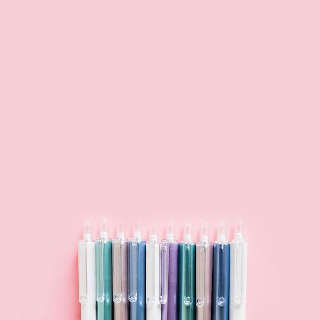 Linha de canetas coloridas em fundo rosa Foto gratuita