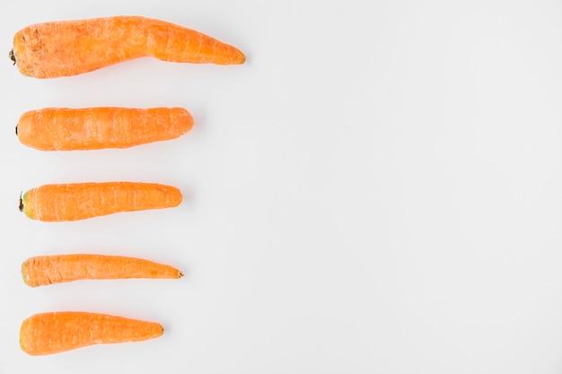 Linha de cenouras frescas em pano de fundo branco Foto gratuita