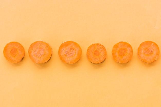 Linha de cenouras frescas fatiadas em fundo laranja Foto gratuita