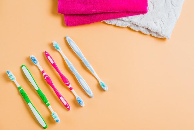Linha de escova de dente com uma toalha rosa e branca em pano de fundo colorido Foto gratuita