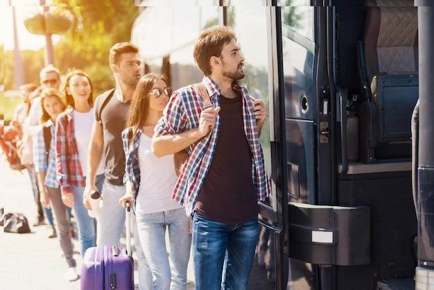 Linha de fila de pessoas de turistas tomando um ônibus. Foto Premium