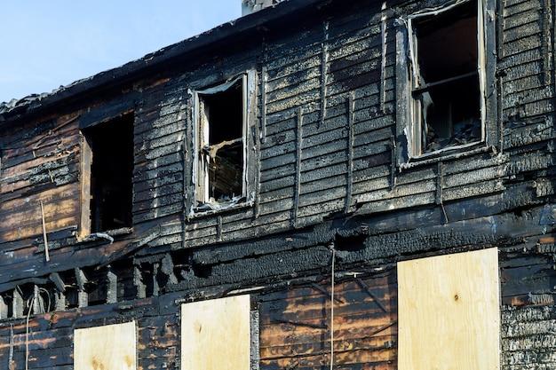 Linha de fogo na frente de uma casa destruída. casa queimada após incêndio Foto Premium