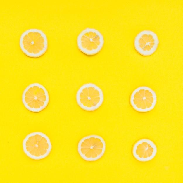 Linha de frutas cítricas em fatias no fundo amarelo Foto gratuita