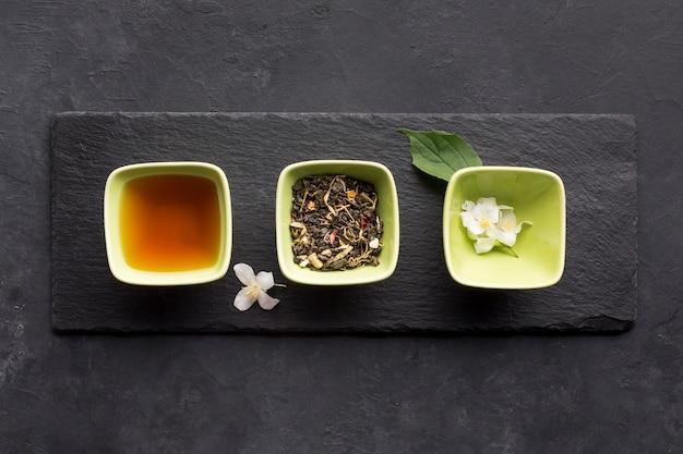 Linha de ingrediente de chá saudável e flor de jasmim branco na pedra ardósia Foto gratuita