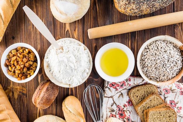 Linha de ingredientes com pães caseiros na mesa de madeira Foto gratuita