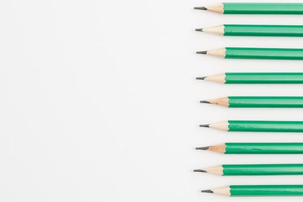 Linha de lápis afiados verdes sobre fundo branco Foto gratuita
