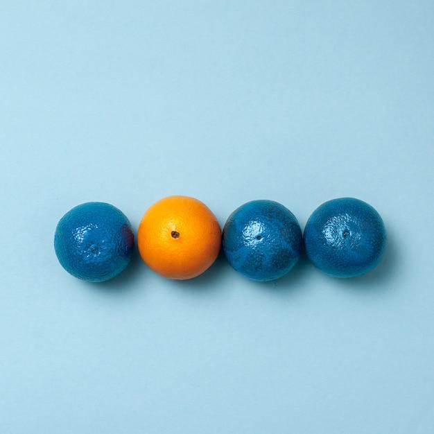 Linha de laranjas azuis com uma laranja limpa Foto gratuita