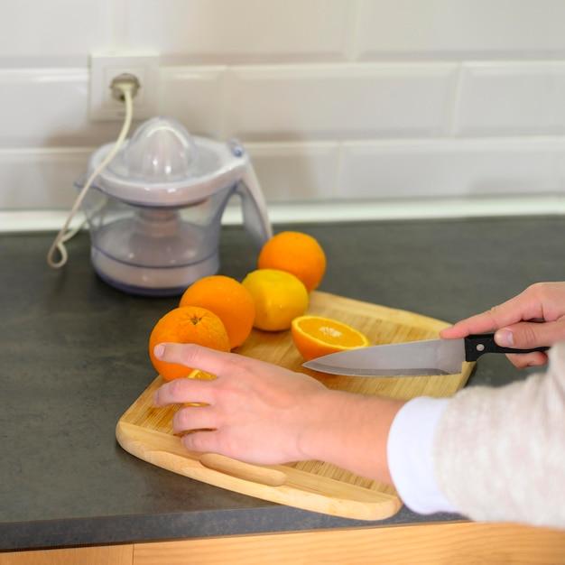 Linha de laranjas e faca na cozinha Foto gratuita