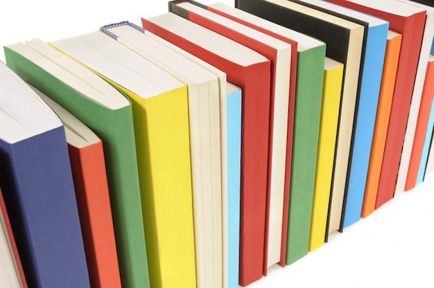 Linha de livros coloridos contra um fundo branco Foto gratuita