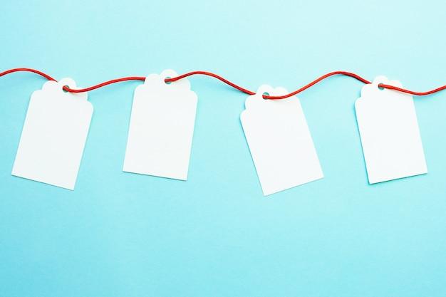 Linha de maquetes de etiquetas de presente em branco na fita vermelha no azul Foto Premium