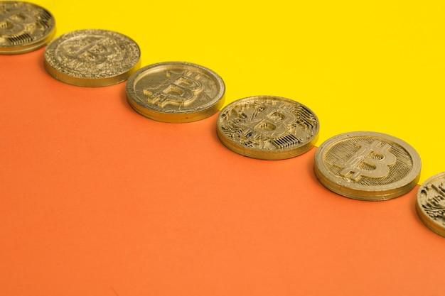 Linha de muitos bitcoins sobre o fundo duplo amarelo e laranja Foto gratuita
