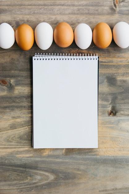 Linha de ovos marrons e brancos perto de bloco de notas em branco na mesa de madeira Foto gratuita