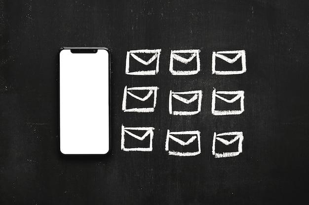 Linha de pequeno ícone de mensagens desenhadas perto do celular na lousa Foto gratuita