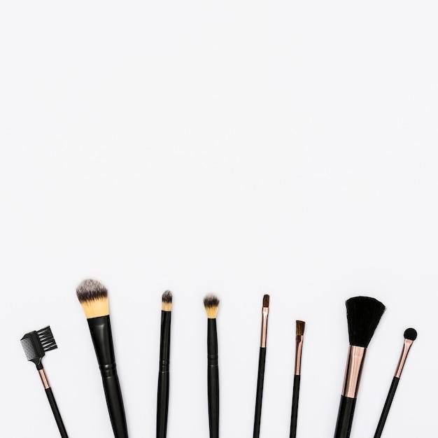 Linha de pincéis de maquiagem com espaço de cópia para escrever o texto no fundo branco Foto gratuita