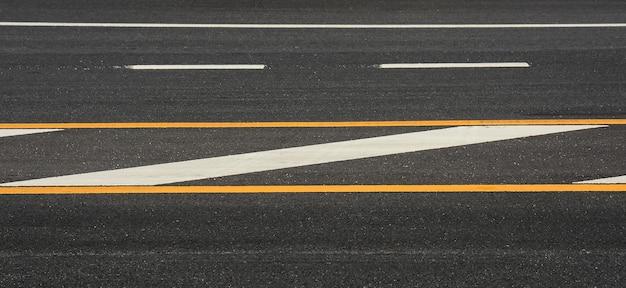 Linha de pintura amarela e branca no asfalto preto. fundo de transporte espacial Foto Premium