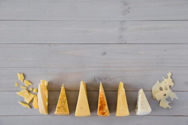 Linha de queijo triangular na mesa de madeira cinza Foto gratuita