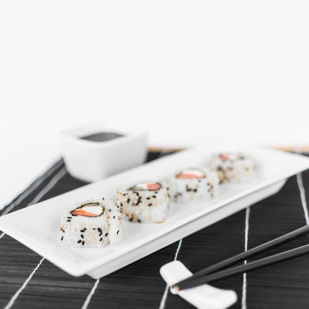 Linha de sushi na bandeja branca com pauzinhos Foto gratuita